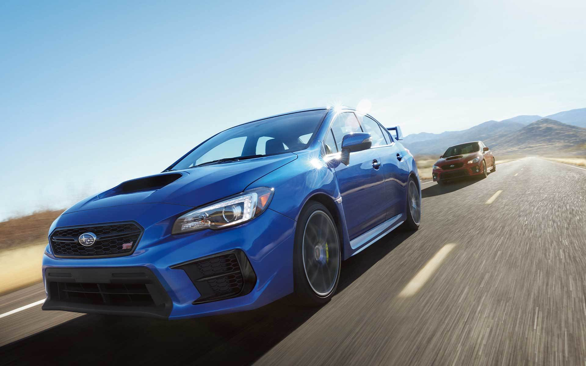 Subaru Image: WRX STI Limited shown in WR Blue Pearl and WRX Premium shown in Pure Red with available Performance Package